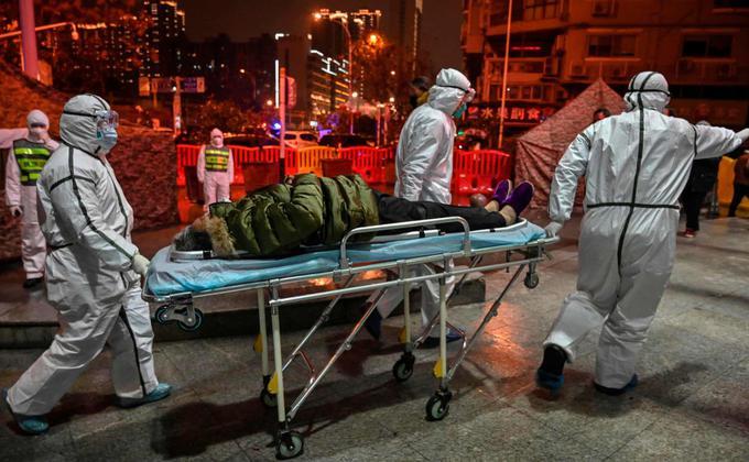 医务人员1月25日将疫情患者送入武汉市红十字会医院。(HECTOR RETAMAL/AFP via Getty Images)
