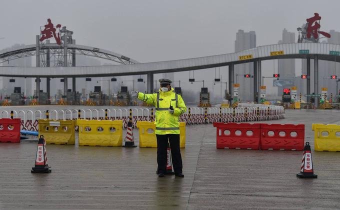 1月25日,一名警察在警方封锁的一条高速公路前,示意人们不准离开武汉市。(HECTOR RETAMAL/AFP via Getty Images)