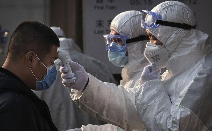 中国天津市武清区人民医院误诊一名武汉肺炎住院患者。图为中国卫生工作人员检查进入北京地铁站乘客的体温。(Kevin Frayer/Getty Images)