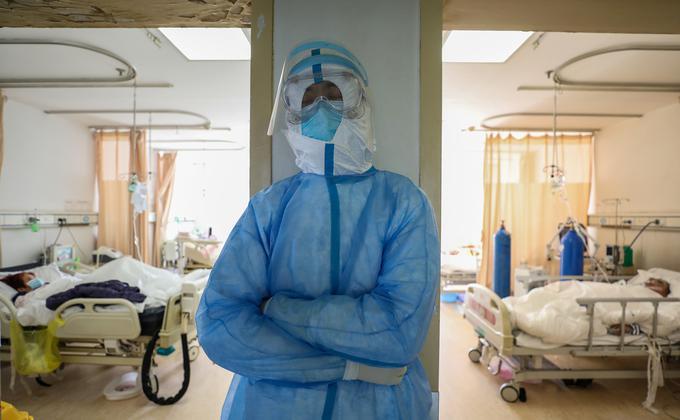图为武汉市红十字会医院的医务人员在隔离病房站靠着休息。(图片来源:STR/AFP via Getty Images)
