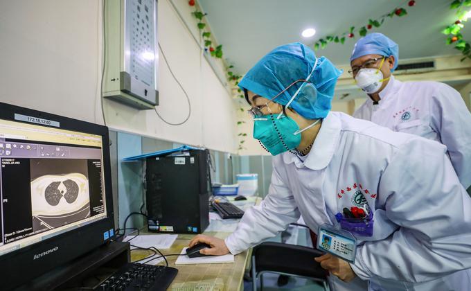 """陆媒披露,当局制定严格的""""标准""""筛选上报病例,导致早期多日无新增确诊案例,延误疫情防控。图为湖北省武汉市一家医院的医生戴着口罩,正在看一位病人拍摄的肺部CT图像。 (图片来源:STR/AFP via Getty Images)"""