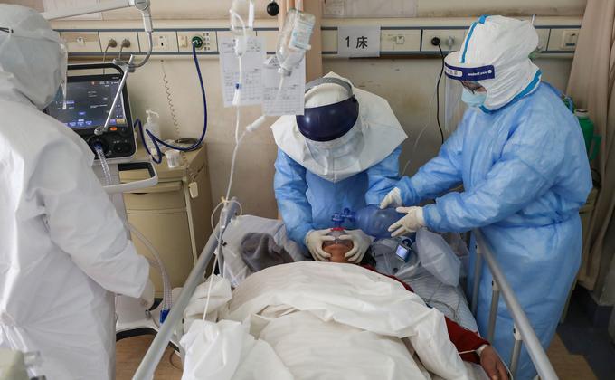 图为武汉市红十字会医院的医务人员正在治疗一名感染COVID-19冠状病毒的病人。 (图片来源:STR/AFP via Getty Images)