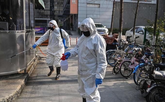 图为穿着防护服的工作人员为湖北省武汉市的一个地区进行消毒防疫工作。(图片来源:HECTOR RETAMAL/AFP via Getty Images)