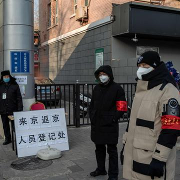 2020年2月3日,戴着口罩的保安和志愿者站在北京居民区的入口处,人们在那里接受身份检查和体温检查。(图片来源:NICOLAS ASFOURI/AFP via Getty Images)