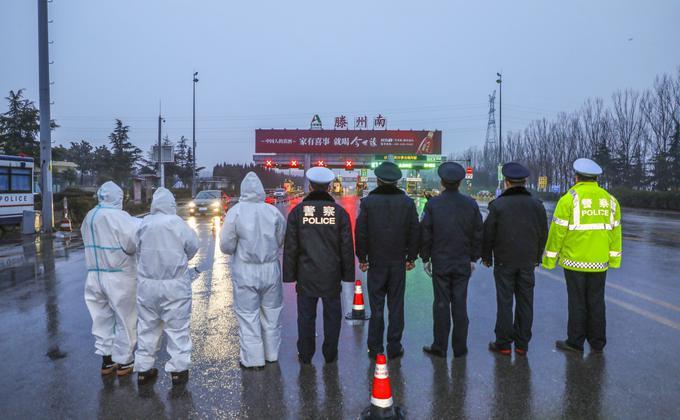黄姓女子刑满释放后,突破重重封锁从武汉返回北京的丑闻,引起巨大争议。图为1月26日,穿着防护服的医务人员与警务人员一起在山东滕州市的高速公路检察站进行防疫工作。(STR/AFP via Getty Images)