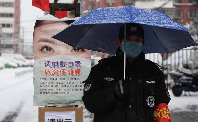 在大陆仍未防疫成功之际,中共官方却忙着出版《大国战疫》书籍,引起许多大陆民众的强烈反感。图2020年2月6日的一个雪天,一名保安在北京某住宅区的入口处打着伞执勤。(图片来源:GREG BAKER/AFP via Getty Images)