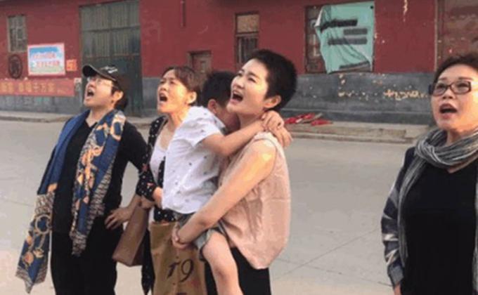 王全璋遭羁押近四年,李文足(抱孩子者)和友人在监狱外呼喊丈夫的名字。(图片来源:推特)