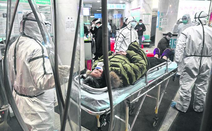 医务人员穿着防护服以帮助阻止致命病毒的蔓延,该病毒始于中國武漢。 (圖片來源:by Hector RETAMAL / AFP/Getty images)