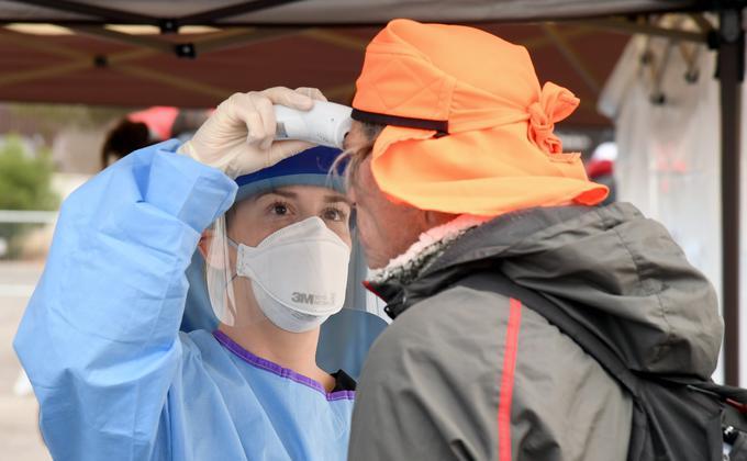 图为美国防疫人员用测温枪为一名无家可归者测量体温。(图片来源:Ethan Miller/Getty Images)