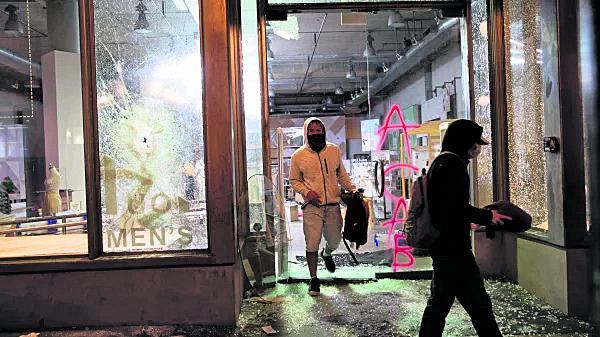 2020年5月30日晚,抢劫者从西雅图的一家被砸碎门面的商店中走出来。 (图:Karen Ducey / Getty Images)